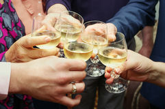 Hands with glasses making chin chin. Closeup of many hands making toast with champagne with selective focus stock photo