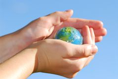 Hands globe. Child holding a globe in hands on blue background Royalty Free Stock Images