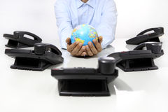Hands globe with office phones on desk, global international sup. Hands globe map with office phones on desk, global international support concept royalty free stock image