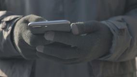 Hands in the glove use a smartphone, texting, typing, message concept, outdoor 60 fps. 4k stock footage