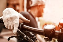 Hands in gloves on bicycle`s handlebars. Mechanic fixing cycle in his workshop. Closeup picture Royalty Free Stock Image