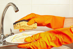 Hands in gloves with dirty plate over the sink in kitchen Stock Photo