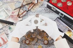 Hands in the gloves hold flip with collector coin. Soft focus background royalty free stock photo