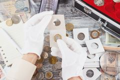 Hands in the gloves hold flip with collector coin. Top view royalty free stock image