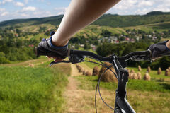 Hands in gloves holding handlebar of a bicycle. Mountain Bike cyclist riding single track. Healthy lifestyle active athlete doing Stock Photography