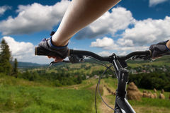 Hands in gloves holding handlebar of a bicycle. Mountain Bike cyclist riding single track. Healthy lifestyle active athlete doing Stock Image