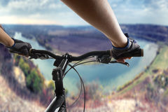 Hands in gloves holding handlebar of a bicycle. Mountain Bike cyclist riding single track. Healthy lifestyle active Stock Image