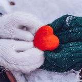 Hands in gloves holding heart closeup on winter snow background. Toned. stock photos