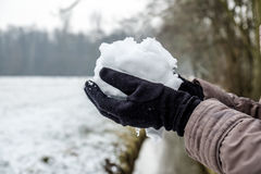 Hands with gloves holding snow Royalty Free Stock Photography