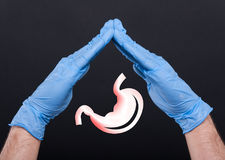 Hands with gloves protecting stomach. As digestive problems concept Stock Images