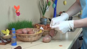 Hands with gloves put onion shell and white egg into sock stock footage