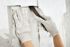 Hands in gloves removing old wallpaper with spatula Stock Photos