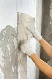 Hands in gloves removing old wallpaper Stock Photos