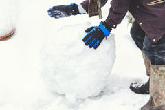 Hands in gloves rolled large snowball Royalty Free Stock Photography