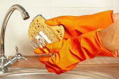Hands in gloves with sponge and dirty cup over the sink in kitchen Royalty Free Stock Image
