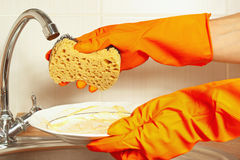 Hands in gloves with sponge and dirty dishes over the sink in kitchen Stock Images