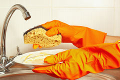 Hands in gloves with sponge and dirty saucer over the sink in kitchen Royalty Free Stock Photos