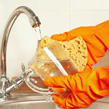 Hands in gloves with sponge wash dirty glass under running water Royalty Free Stock Images