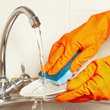 Hands in gloves with sponge wash the dishes under running water in kitchen Stock Image