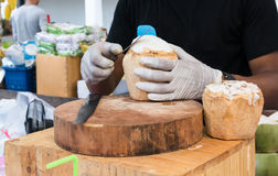 Hands with gloves trimming coconut flesh with long knife on wood Royalty Free Stock Photo