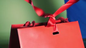 Hands in gloves untie a red ribbon of a luxury gift bag. Clip stock video footage