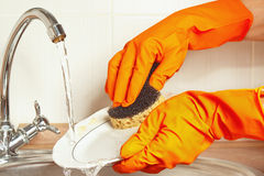 Hands in gloves wash the dirty dishes under running water in kitchen Royalty Free Stock Photos