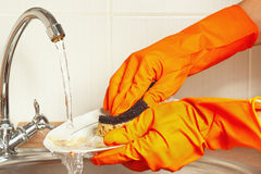 Hands in gloves wash the dishes under running water in kitchen Royalty Free Stock Photos