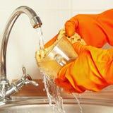 Hands in gloves wash the glass under running water in kitchen Stock Photos