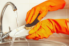 Hands in gloves wash the plate under running water in kitchen Royalty Free Stock Photography