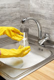 Hands in gloves washing drinking glass under running tap water. Close up of female hands in yellow protective rubber gloves washing drinking glass under running stock images