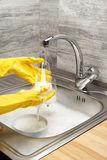 Hands in gloves washing drinking glass under running tap water. Close up of female hands in yellow protective rubber gloves washing drinking glass under running royalty free stock photography