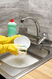 Hands in gloves washing tableware with sponge and detergent. Close up of female hands in yellow protective rubber gloves washing tableware with green cleaning royalty free stock photography