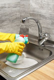 Hands in gloves washing tableware with sponge and detergent. Close up of female hands in yellow protective rubber gloves washing tableware with green cleaning stock photography