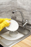 Hands in gloves washing white plate against kitchen sink. Close up of female hands in yellow protective rubber gloves washing white plate with pink cleaning stock images