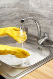 Hands in gloves washing wine glass under running tap water. Close up of female hands in yellow protective rubber gloves washing wine glass under running tap Stock Photos