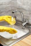 Hands in gloves washing wine glass under running tap water stock photos