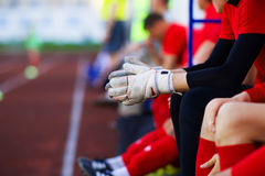 Hands goalkeeper. Gloves closeup. Sitting on the bench Stock Photography