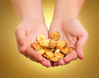Hands with gold coins. On yellow background royalty free stock photography