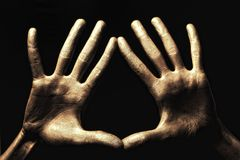 Hands in gold paint on black background Stock Photos