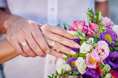 Hands with gold rings bride and groom on wedding bouquet Stock Photos