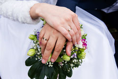 Hands with golden rings and bridal bouquet Stock Photo