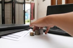 Hands grabbed coins on the table, version 2. Hands grabbed coins on the table, with laptops and financial reports, version 2 royalty free stock photo