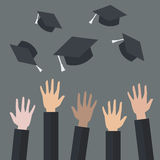 Hands of graduates throwing graduation hats in the air Stock Image