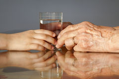 Hands of grandmother and grandchild and water Stock Photography