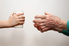 Hands of grandmother and grandchild - water Stock Photo