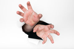 Hands grasping through hole. A man's hands reach through a hole torn in a white paper background and are grasping menacingly toward the camera Royalty Free Stock Photo