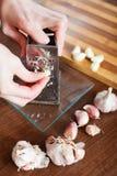 Hands  grating garlic Royalty Free Stock Photography