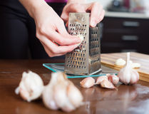 Hands  grating garlic with grater Royalty Free Stock Photo