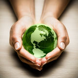 Hands with green Earth globe stock photos
