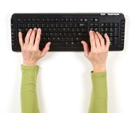 Hands in green jacket and black keyboard. On white background Stock Photography